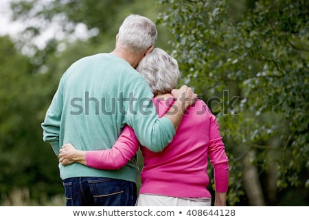 Stock photo: Rear view of senior couple standing with arm around in the park