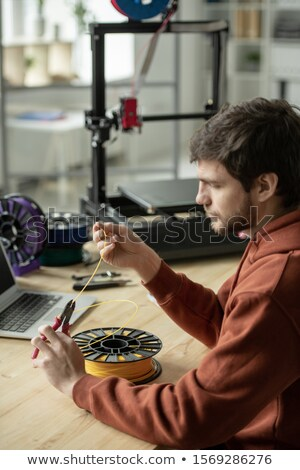 Creative man sitting by table and cutting piece of yellow filament for printing Stock photo © pressmaster
