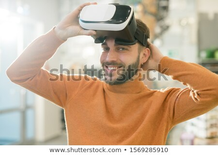 happy young man looking at you with smile while taking off vr headset stock photo © pressmaster