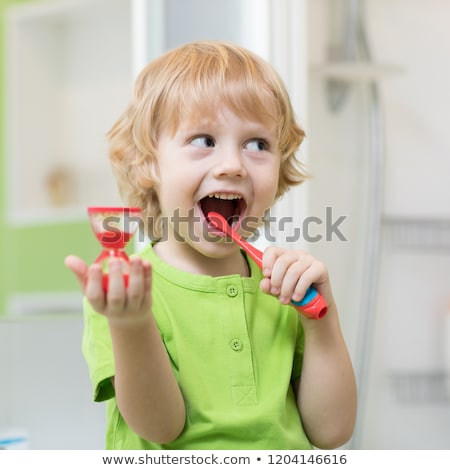 Boy cleans his teeth in the morning and plays with a toothbrush Stock photo © ElenaBatkova