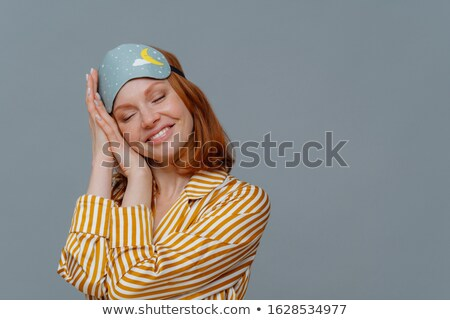 Satisfied ginger woman has nap, sees pleasant dreams, tilts head on palms, smiles gently with closed Stock photo © vkstudio