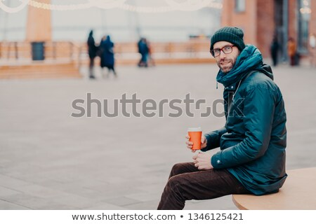 Sideways shot of handsome male adult dressed in street clothes, enjoys aromatic beverage, poses outd Stock photo © vkstudio
