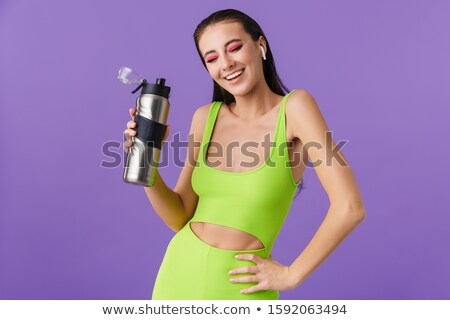 Photo of nice laughing woman using earpods and holding water bottle Stock photo © deandrobot