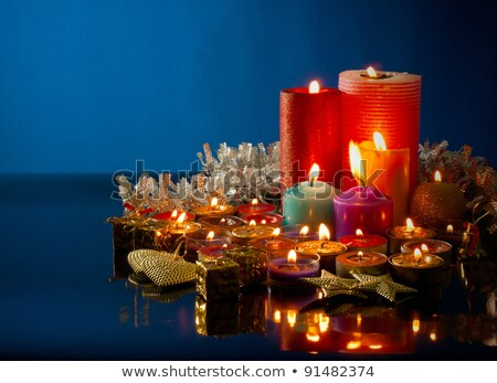 a lot of burning colorful candles against dark blue background stock photo © andreykr