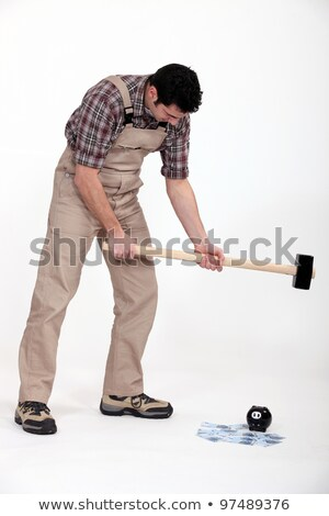 portrait of journeyman breaking money box with hammer Stock photo © photography33