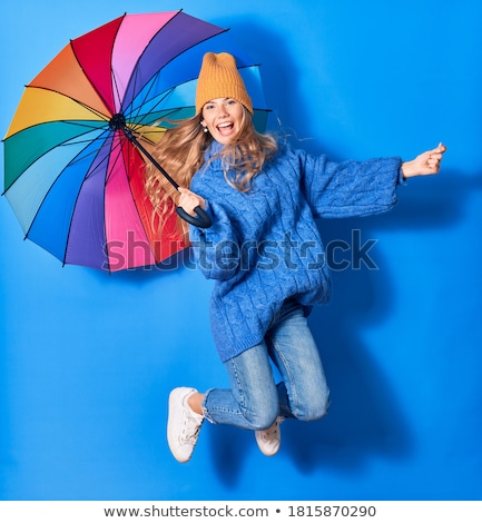 Studio Portrait Of Young Woman Jumping In Air with umbrella  Stock photo © danielkrol