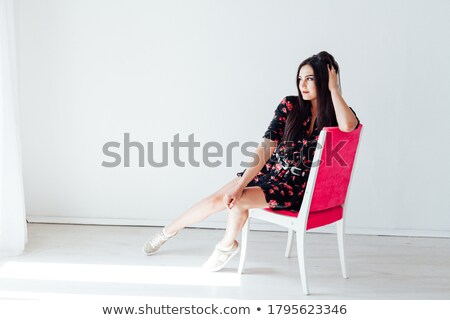 Stunning brunette sitting and posing on a chair in fashion dress  Stock photo © danielkrol