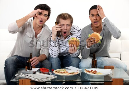ストックフォト: Three Lads Cringing At The Television