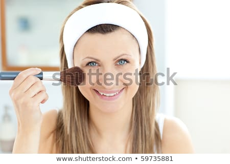 Smiling caucasian woman putting powder on her face smiling at the camera in the bathroom at home stock photo © wavebreak_media