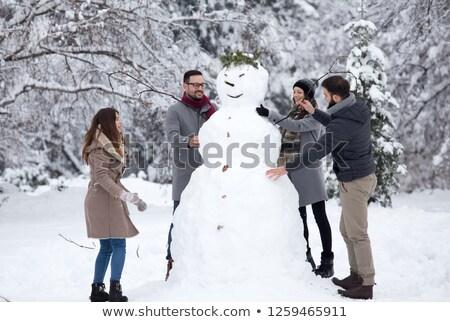 two happy girls building a snowman stock photo © balasoiu