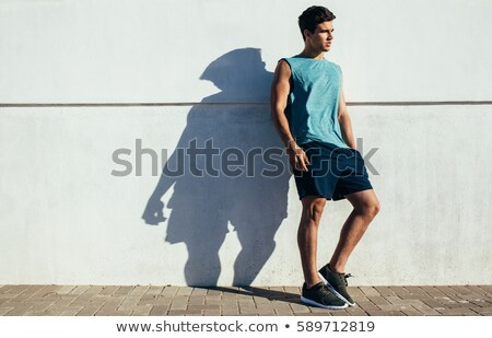 handsome man resting on the sidewalk, leaning against a wall Stock photo © feedough