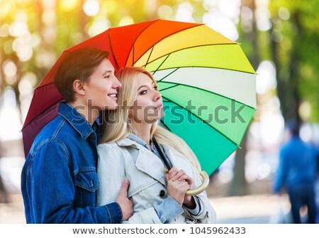 Two attractive friends walking with umbrellas Stock photo © majdansky