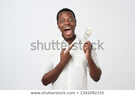 man's hand holding a one hundred dollar bill Stock photo © ozaiachin