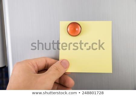 Person Holding Note Sticked On Fridge Door stock photo © AndreyPopov
