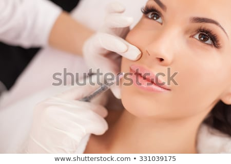 young caucasian woman receiving an injection of botox from a doctor stock photo © ambro