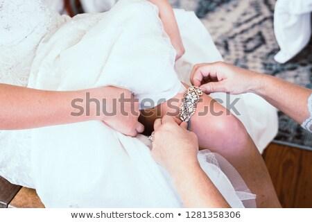 wedding garter in hands on leg Stock photo © konturvid