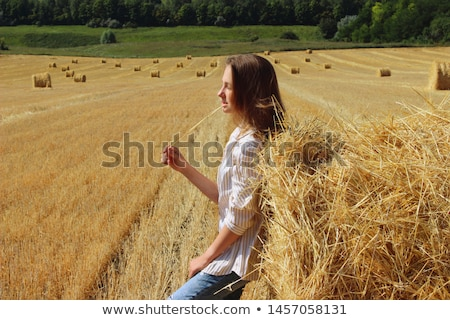 Young beautiful woman relaxes on hay Stock photo © Aikon