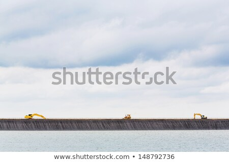 Backhoe on dam crest Stock photo © smuay