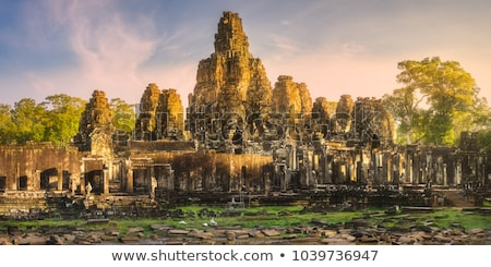 Gigante pedra faces templo Camboja pôr do sol Foto stock © Mikko