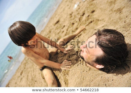 real happiness playing on beach my dad under the sand stock photo © zurijeta