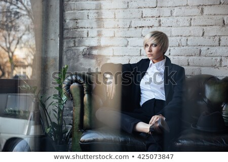 Stylish blonde girl thinking in cafe Stock photo © deandrobot