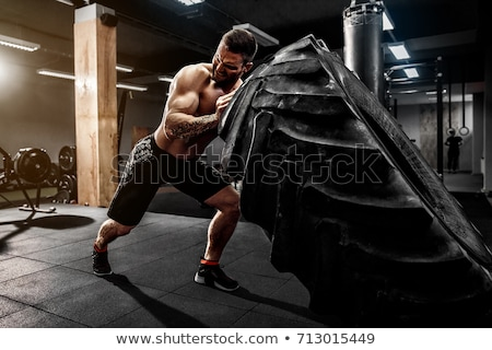 Athletic man with wheel Stock photo © deandrobot