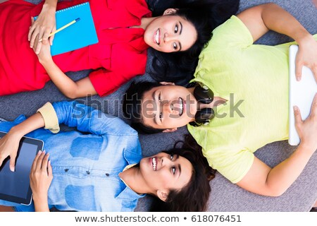 Three funny young employees or students lying down on the floor Stock photo © Kzenon