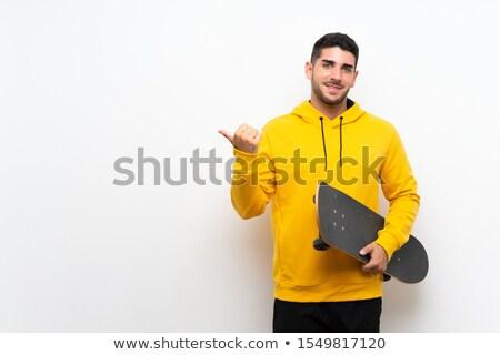 Retrato sonriendo hombre skateboard senalando Foto stock © LightFieldStudios