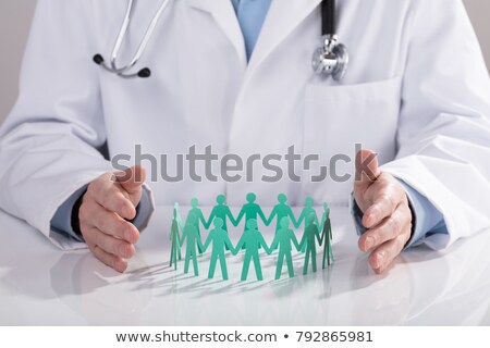 Doctor Protecting Paper Cut Out Figures On Desk Stock photo © AndreyPopov