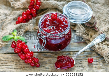 Fruit jam with spoon and berries in glass on a table stock photo © hraska