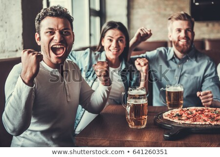 Fans of a sports team watching game in bar Stock photo © Kzenon