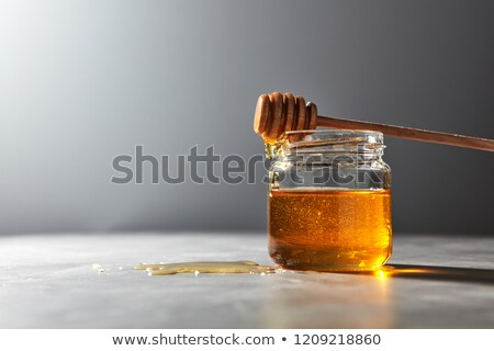 Fragrant natural organic honey dripping from wooden stick into a gray kitchen table. Jewish New Year Stock photo © artjazz