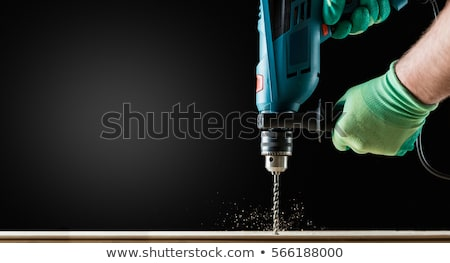 carpenters with drill drilling plank at workshop stock photo © dolgachov