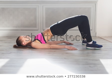 young woman doing gymnastics bridge pose in fitness studio stock photo © boggy