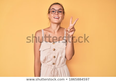 Portrait of cheerful brunette girl with two buns pointing finger Stock photo © deandrobot
