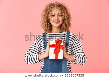 Photo of pleased curly woman 20s holding present box while stand Stock photo © deandrobot