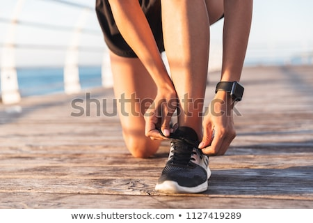 Photo of slim european sportswoman 20s in tracksuit squatting, a Stock photo © deandrobot