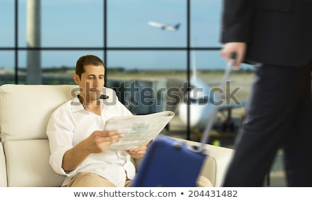 a man in the lounge area at the airport is waiting for his plane stock photo © galitskaya