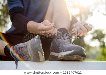 Male athlete tying shoe laces in minimalistic barefoot sneakers  Stock photo © snowing