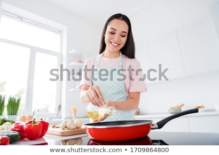 pretty young woman cooking in her modern kitchen stock photo © lightpoet