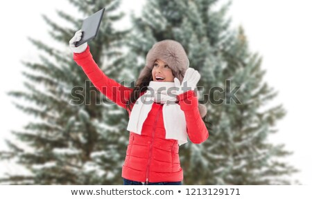 Stockfoto: Woman With Tablet Pc Over Fir Trees In Winter