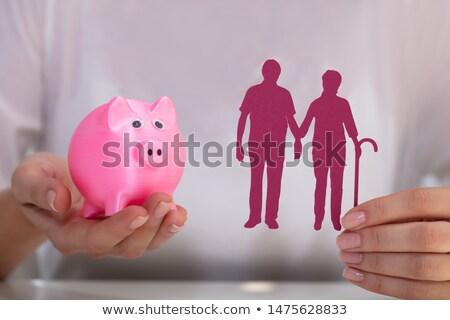 Foto stock: Woman Holding Piggy Bank And Cutout Figure