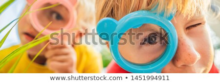 Stock photo: Boy and girl are looking in a magnifying glass against the background of the garden. Home schooling