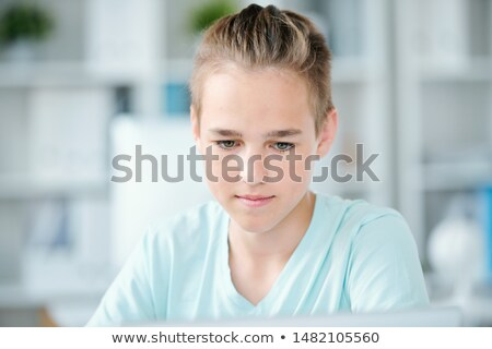 Cute middle school boy concentrating on individual work at school Stock photo © pressmaster