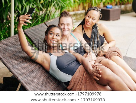 Attractive woman with smartphone resting on chaise lounge Stock photo © dash