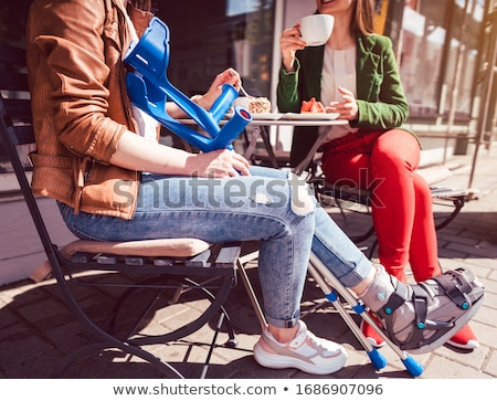 Stock photo: Two friends in a park, one with a broken feet and crutches