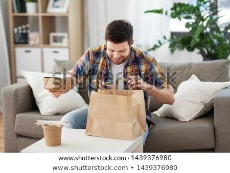 smiling man unpacking takeaway food at home Stock photo © dolgachov