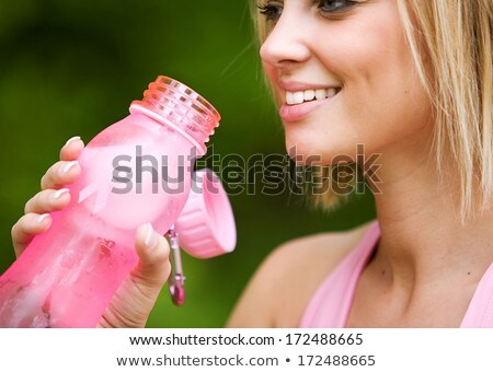 Smiling fit woman holding plastic water bottle Stock photo © photosebia