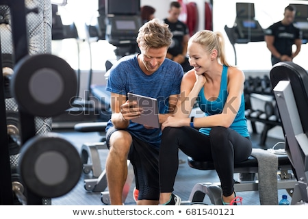 Foto stock: Trainer using digital tablet while talking to woman