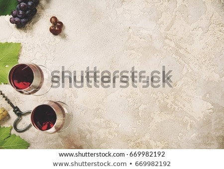 Glass of red wine with dark grapes on marble board with corkscrew opener and cork on black backgroun Stock photo © DenisMArt